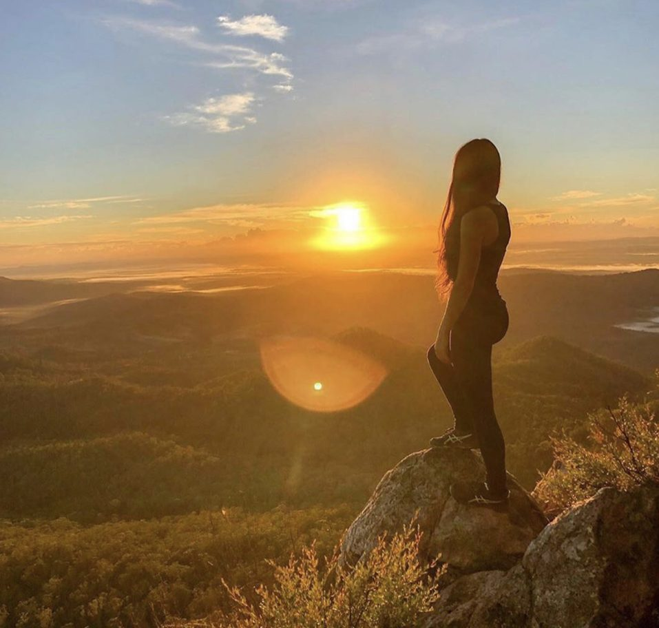 Woman in the sun at top of mountain
