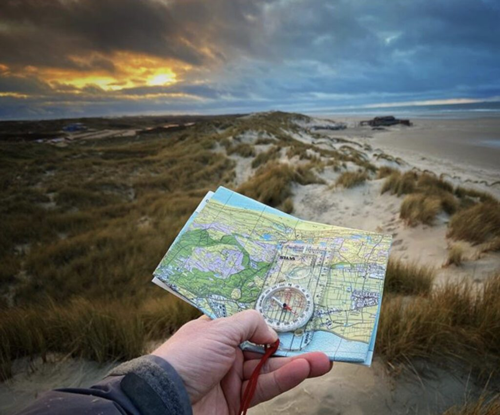 Map and compass held in hand in front of beach