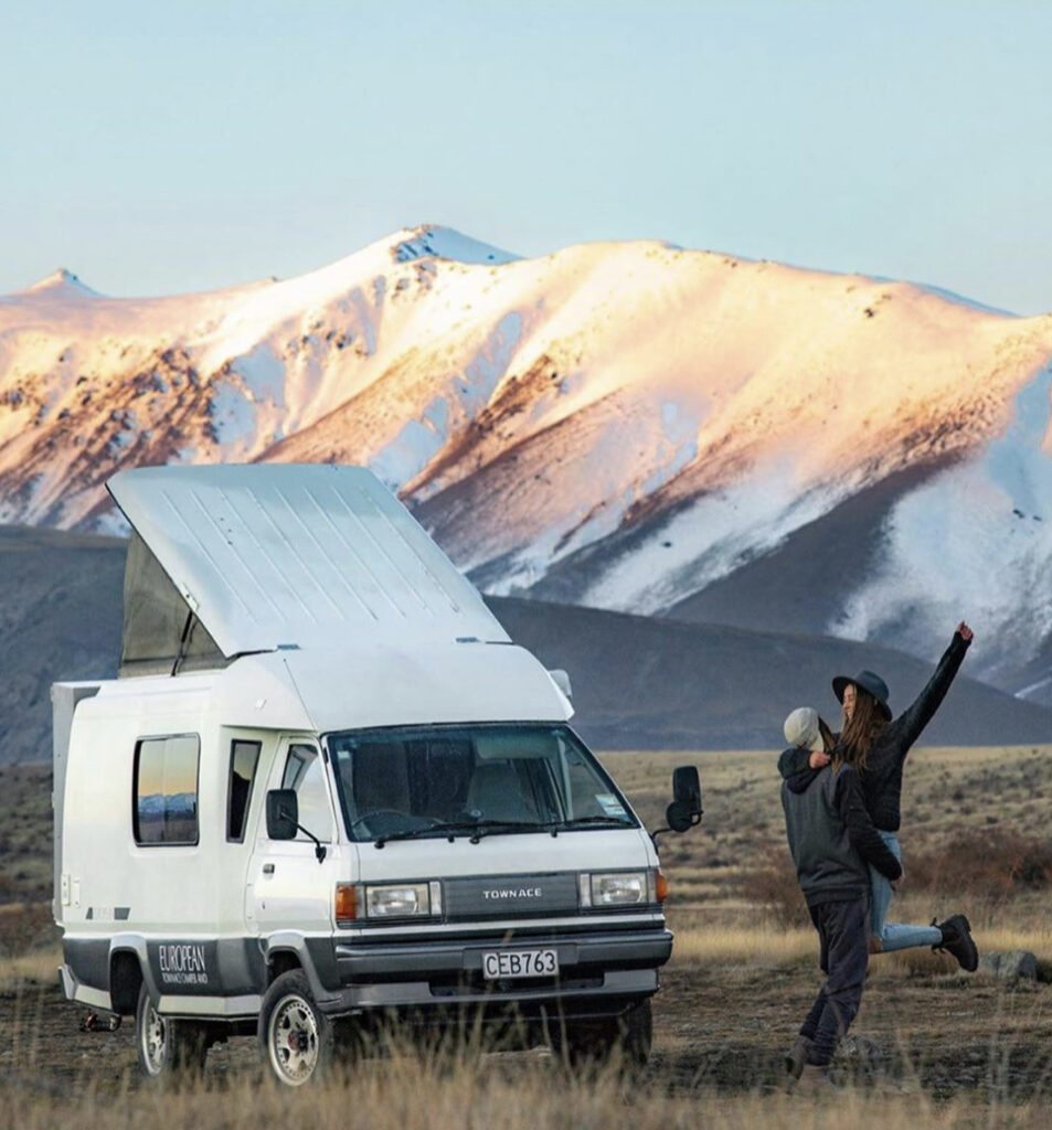 Van Camping - pop top van in front of mountains with couple next to it
