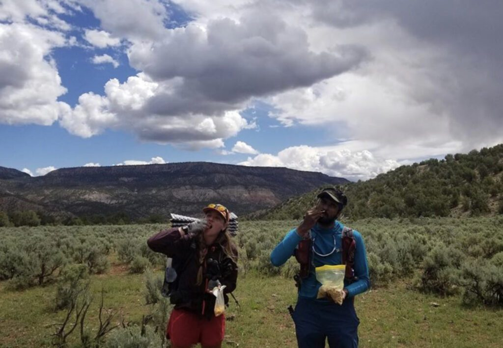 What to bring on a hike: man and woman stopping for a snack on a hike
