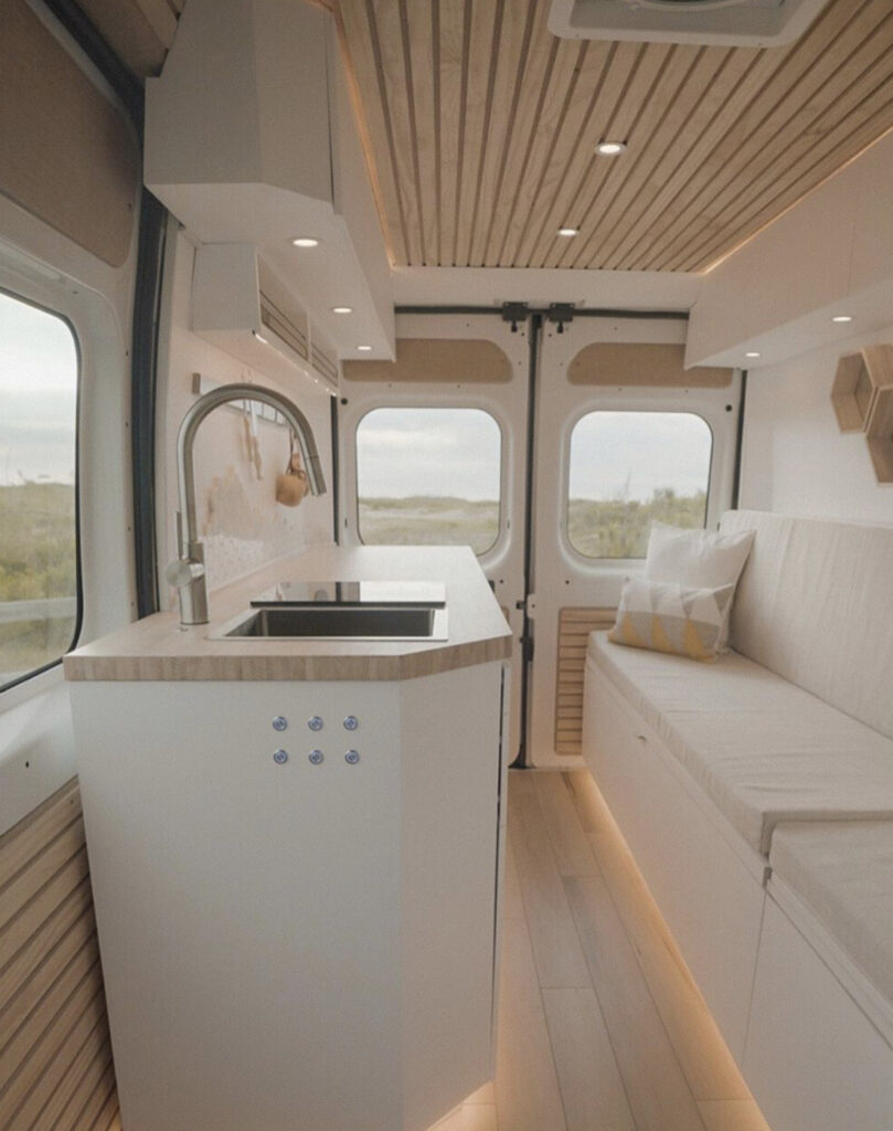 White interior of camper with kitchen and seat