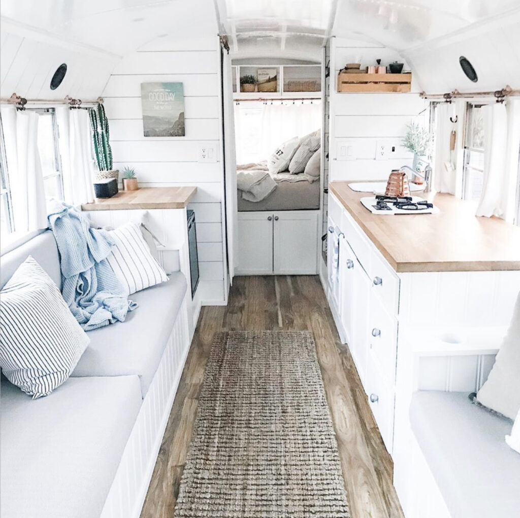 All white bus with white kitchen, walls and ceiling.