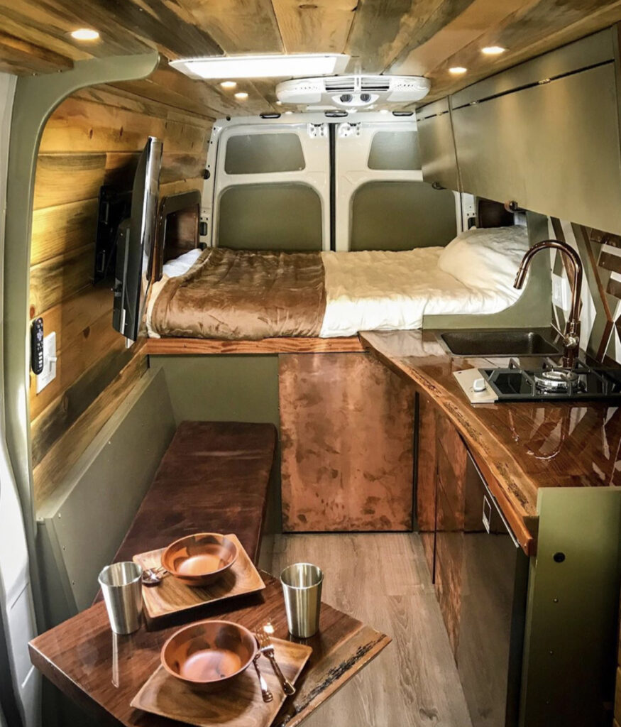 Dark green van with bed at backa nd kitchen and seating in front
