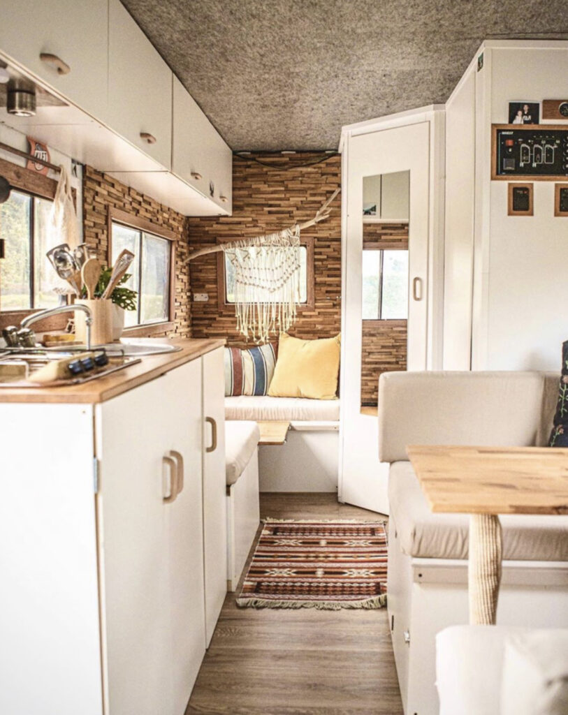 Camper conversion with white kitchen and lots of seating space