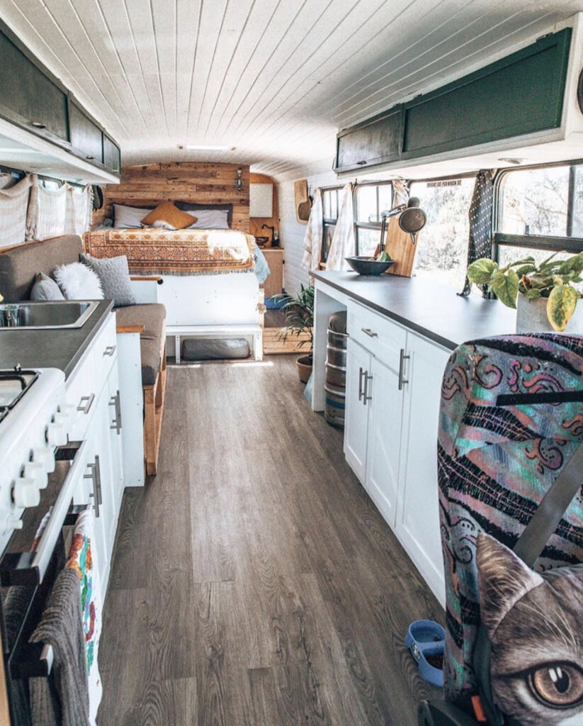 Open plan bus conversion with kitchen sofa and bed