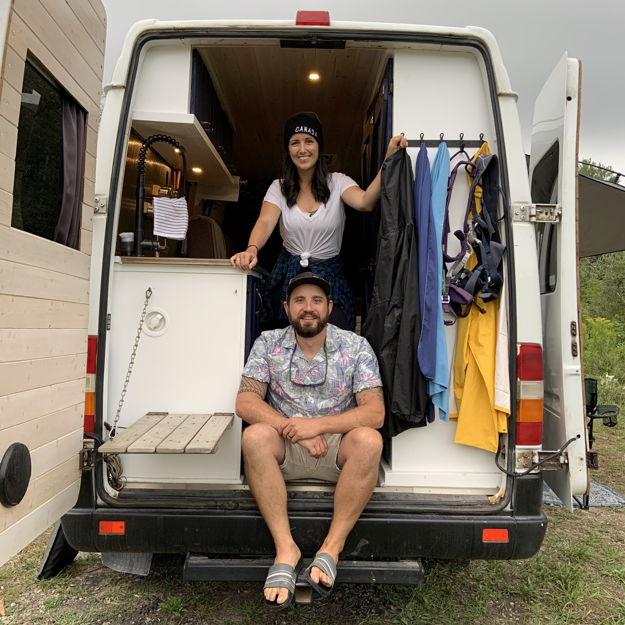 Chet and Sarah smiling at the camera and standing at the back doors of the van.